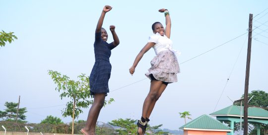 Two teenage girls jumping in the air