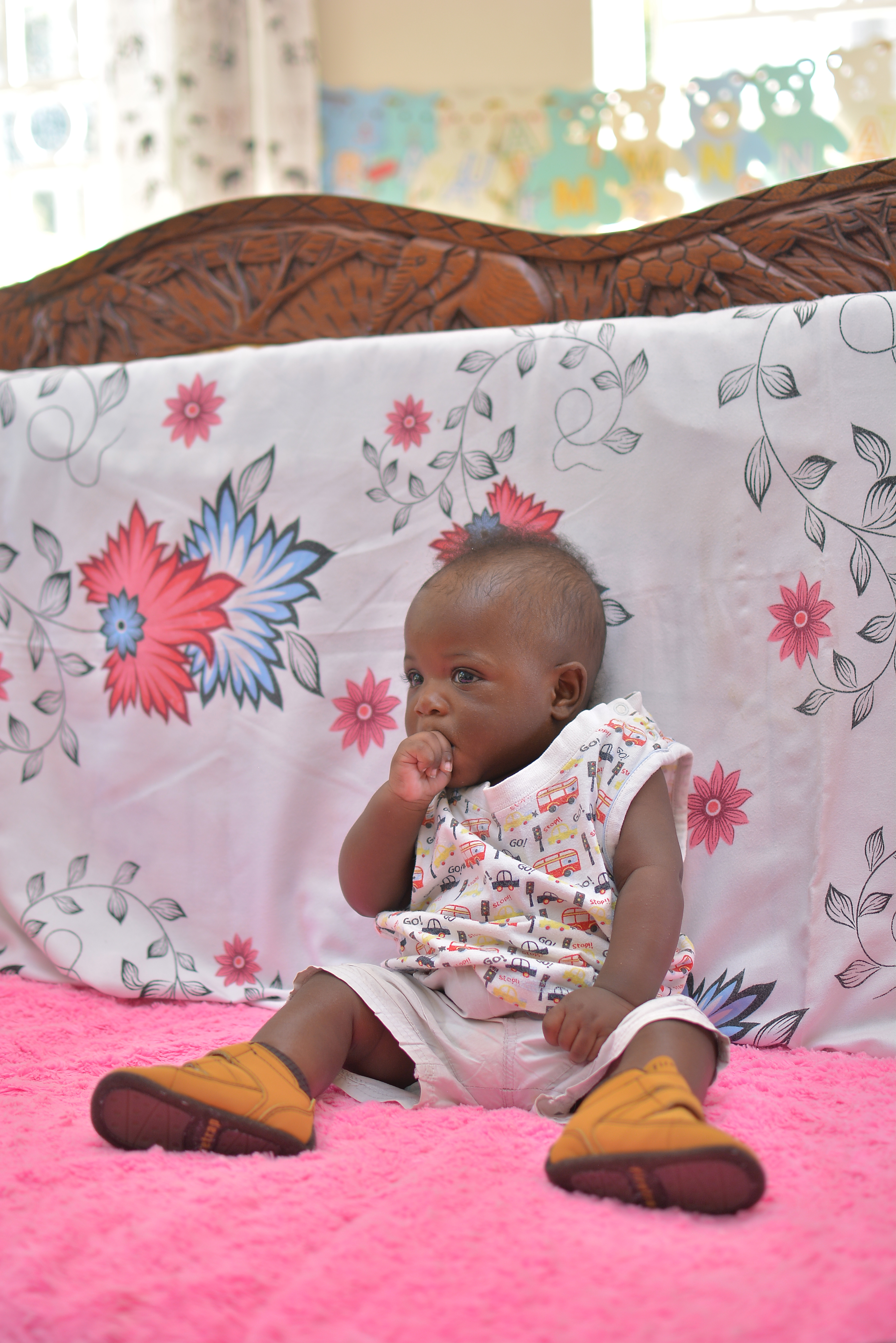Young child sitting on bed